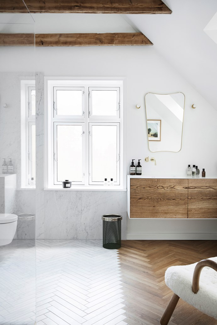 The bathroom, with its marble and timber floor, is Pernille's favourite room in the house; the family often hangs out here when Billy has his bath. The mirror is Gubi and the chair is by Philip Arctander.