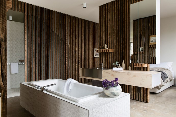 """One of the suites at Drift House. The bedroom features an [open-concept bathtub](https://www.homestolove.com.au/are-bathtubs-in-bedrooms-the-next-big-design-trend-6824