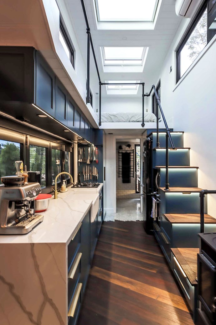 """The tiny home's interior features hardwood flooring, a full-sized kitchen and stairs with LED strip lighting. Skylights run along the length of the ceiling. *Photo courtesy of: [Living Big in a Tiny House](https://www.livingbiginatinyhouse.com/