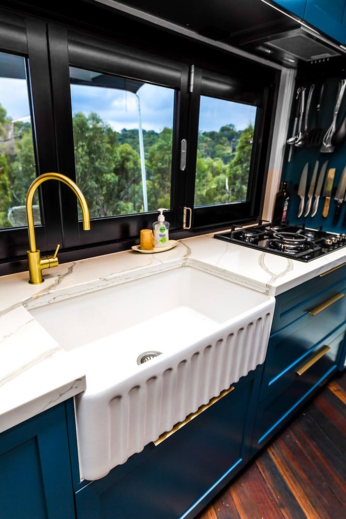 """Modern classic finishes were selected for the kitchen. Brass hardware and a large sink make the space stylish and functional, while a servery window splashback dissolves the distinction between indoors and out. *Photo courtesy of: [Living Big in a Tiny House](https://www.livingbiginatinyhouse.com/