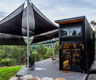 Tiny house with black exterior and large outdoor deck