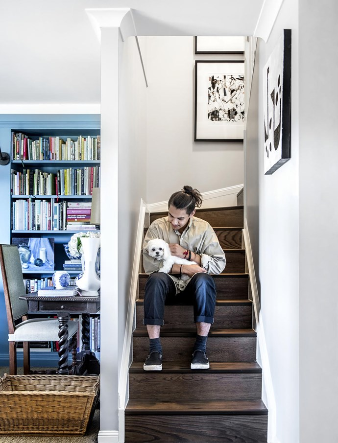Nate and Helen take time out on the stairs leading to the bedrooms. Bespoak micro veneer flooring in Tweed, Carpet Court. Artworks (from left) by John Neeson and Sue Carroll.