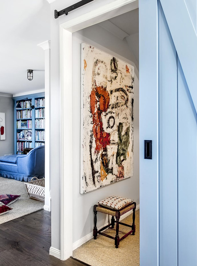 Converting the garage created a small television room off the entry hall. Its blue sliding door echoes the living room bookshelf. Artwork by John Taylor.