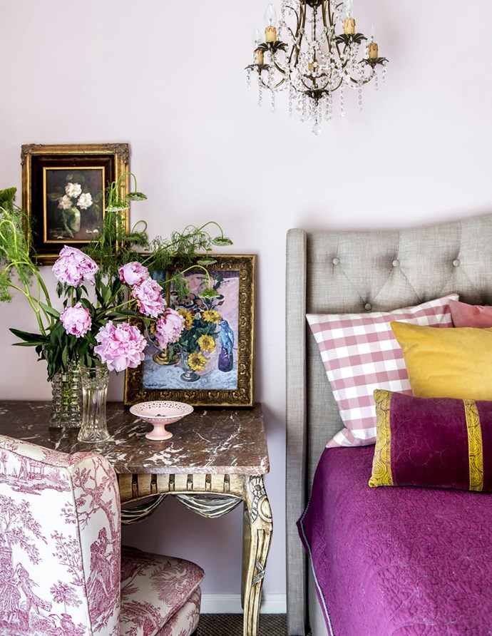 An antique table, chandelier and chair reupholstered in an English toile fabric, vintage artworks and Taubman's Alden Pink walls create this charming room. Coverlet, Anthropologie