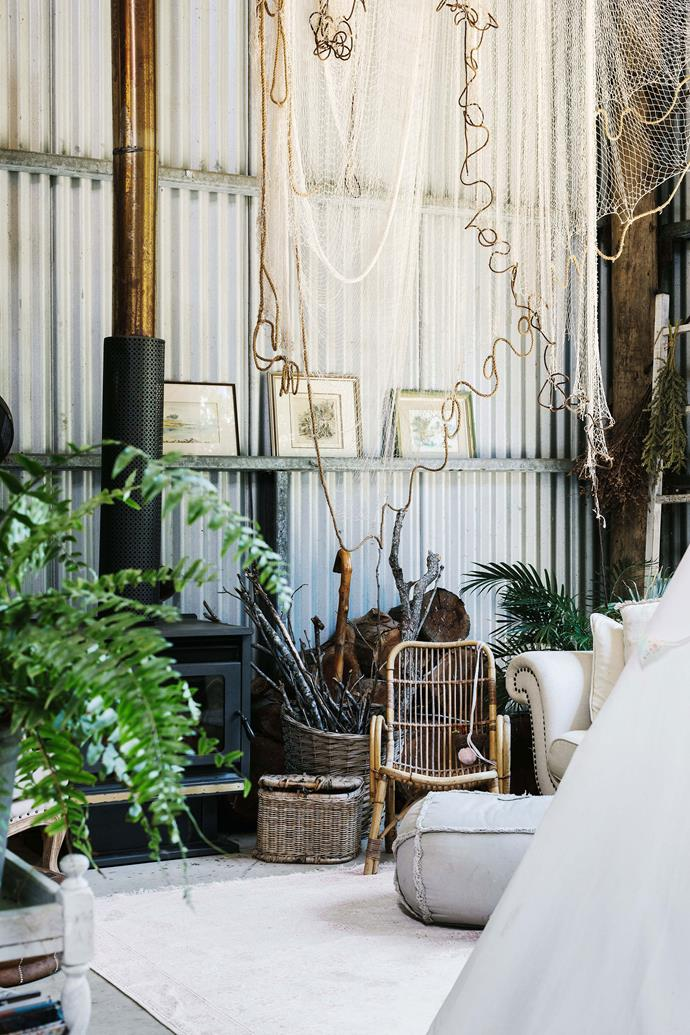 The living room fireplace was a Gumtree find. Lisa tackled the large open-plan interior of the shed by creating a series of zones. Fishing nets (a nod to the home's original owner, a boat-builder) hang from the ceiling to further define distinct areas of the home.