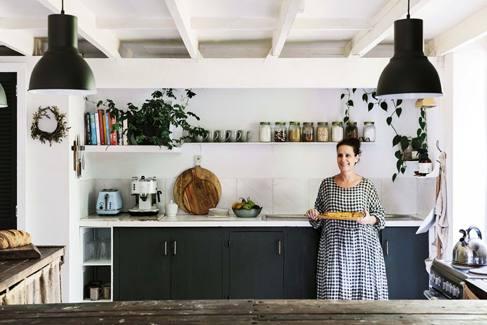 """The kitchen features dark coloured cabinetry as well as hessian curtains sewn by Lisa herself. The 'Hugo' pendant lights in charcoal were purchased from [Bunnings](https://www.bunnings.com.au/brilliant-240v-42w-23cm-hugo-charcoal-pendant-light_p7071447