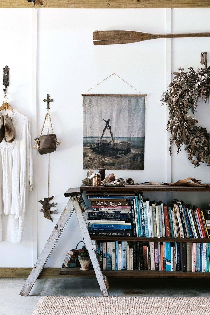 """In the hallway, a makeshift shelf holds the family's collection of books. The shelf was constructed by Lisa from an old step-ladder, and some timber floorboards. The artwork, a linen print, was purchased from [Captain's Rest in Tasmania](https://www.homestolove.com.au/tasmania-airbnb-captains-rest-13981