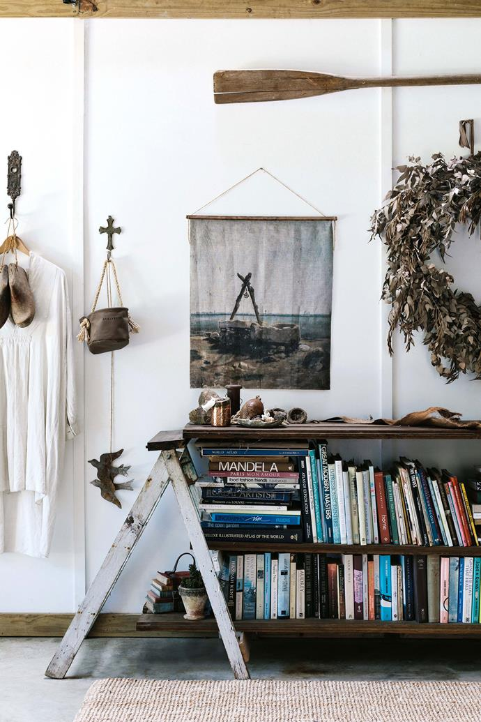 "In the hallway, a makeshift shelf holds the family's collection of books. The shelf was constructed by Lisa from an old step-ladder, and some timber floorboards. The artwork, a linen print, was purchased from [Captain's Rest in Tasmania](https://www.homestolove.com.au/tasmania-airbnb-captains-rest-13981|target=""_blank""
