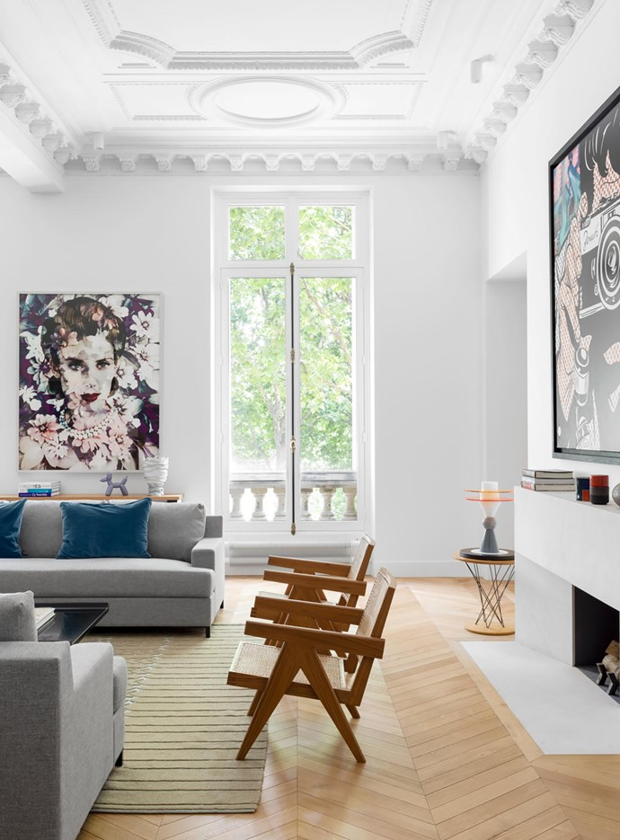 'Don Juan' sofas from Christian Liaigre with cushions from Élitis in the living room. The artwork to the left of the window is a photograph by Valérie Belin. Beyond the fireplace, an Ettore Sottsass lamp stands on a table by Isamu Noguchi.