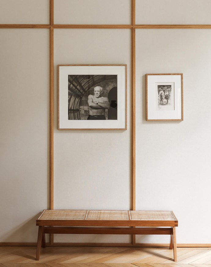 In the main bedroom, the walls are clad in linen. The teak and cane bench was designed by Pierre Jeanneret in the 1950s. The portrait of Picasso was taken by André Villers. Next to it is a drawing by Gérard Garouste.