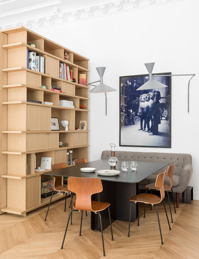 The custom dining table has a Corian top and metal base. The dining chairs were designed by Arne Jacobsen. The custom storage and shelving unit is made from oak. 'Coogee Cotton' sofa from Sentou in Paris. Cassina 'Marseille' wall lights by Le Corbusier. The photo is *Les Lions* by Jean-Pierre Khazem. The carafe on the table is by Tom Dixon.