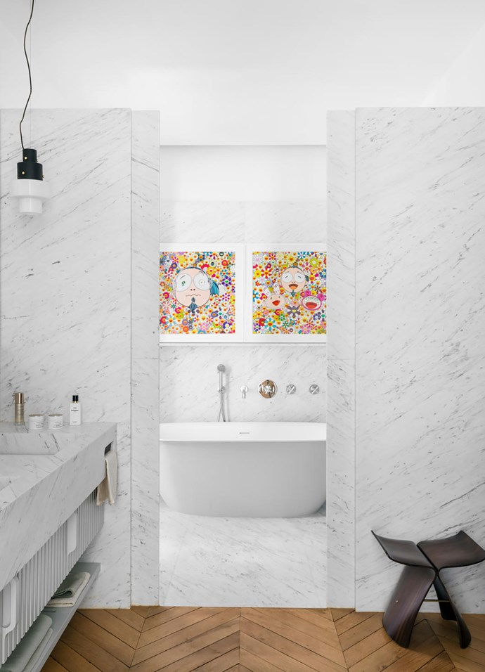 The main bathroom is clad in Carrara marble. 'Butterfly' stool by Sori Yanagi. Beta Essential bath from Hidrobox. The two screenprints are by Takashi Murakami. 'Roma' tap and bath fixtures from Stella.