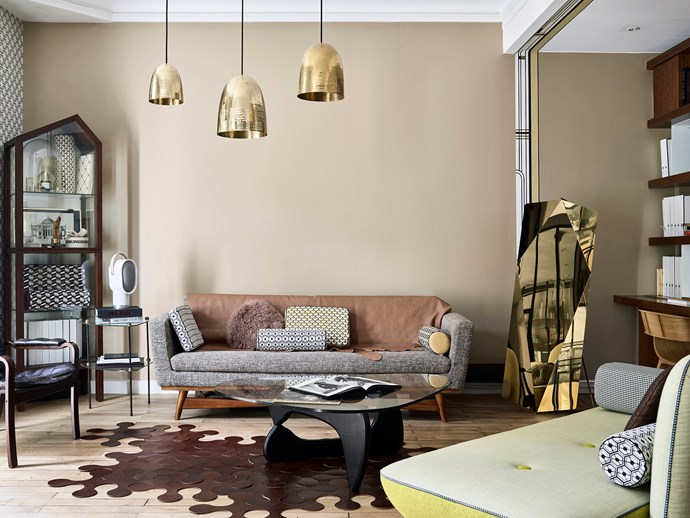 The Red Edition wood and fabric sofa, Isamu Noguchi coffee table, Nymphe brass mirror, Molecules puzzle rug and pendant from Original BTC were all chosen for their visual impact.