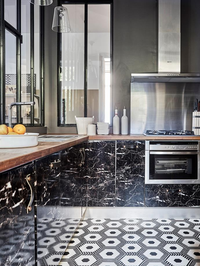 Beyond an iron and glass-framed window lies the kitchen, complete with custom-designed faux marble cabinetry, leather handles, chrome appliances and Beauregard geometric cement tiles.