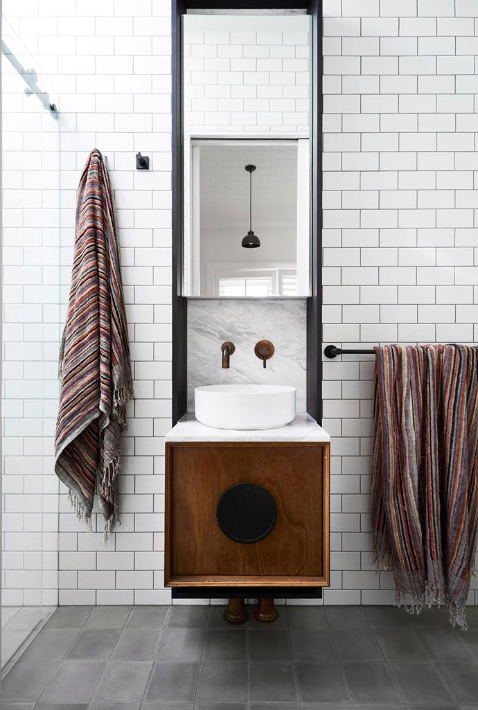White subway tiles laid in a tight horizontal brick bond pattern pop against the dark grout. *Photo:* Armelle Habib / *bauersyndication.com.au*
