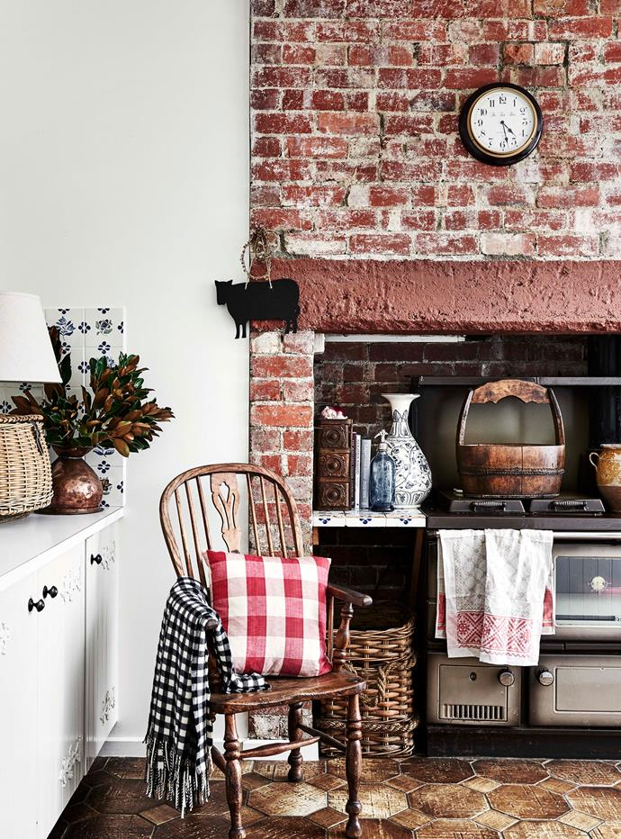 The kitchen's existing red-brick hearth and tiled splashback were maintained in the renovation of this Tudor-style home in Victoria.