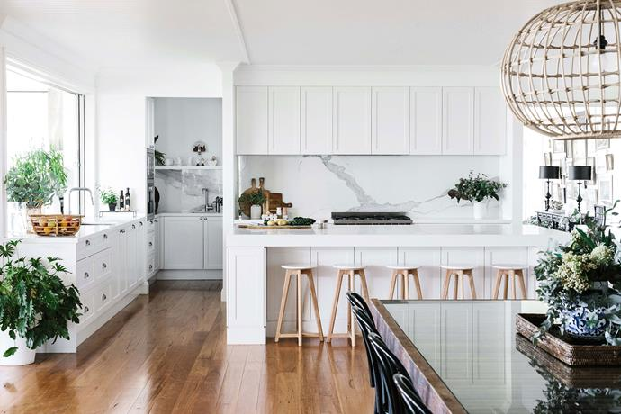An all-white colour scheme is elevated by QuantumSix+ marble-look porcelain splashbacks in the cooking zone and butler's pantry  of this kitchen.