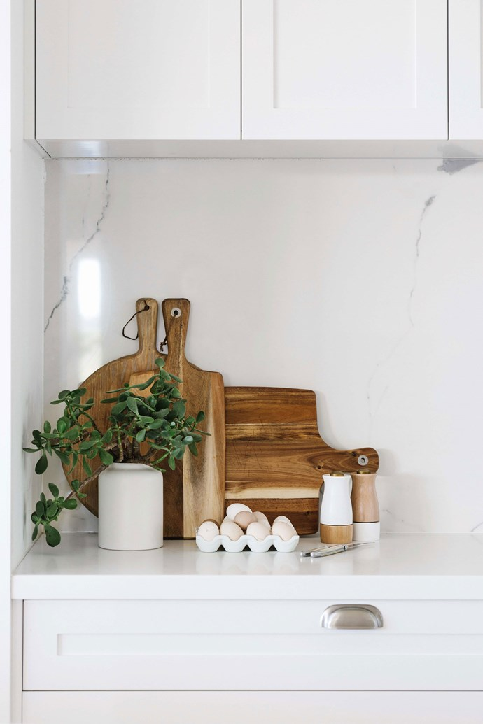 A display of timber chopping boards breaks up the expanse of white used in this kitchen. *Photo: Marnie Hawson*