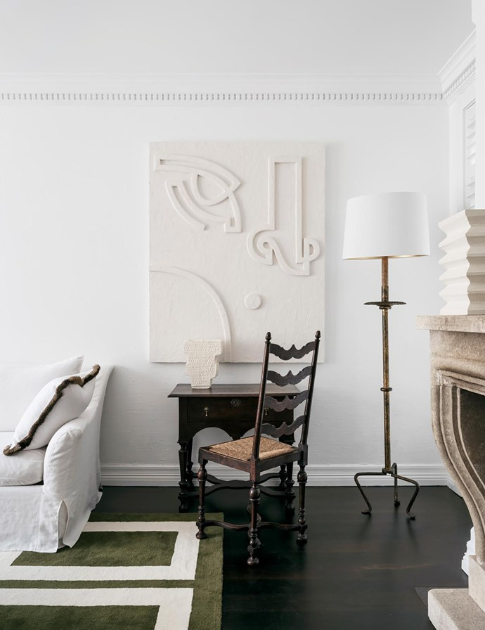 In the living room, an artwork by Angie Pai is perfectly in keeping with the neutral palette. Standard lamp from The Country Trader. Vases by Den Holm. Custom-made sofa in Raffles linen sits on a custom rug. Cushion finished in fringing by Kelly Wearstler.