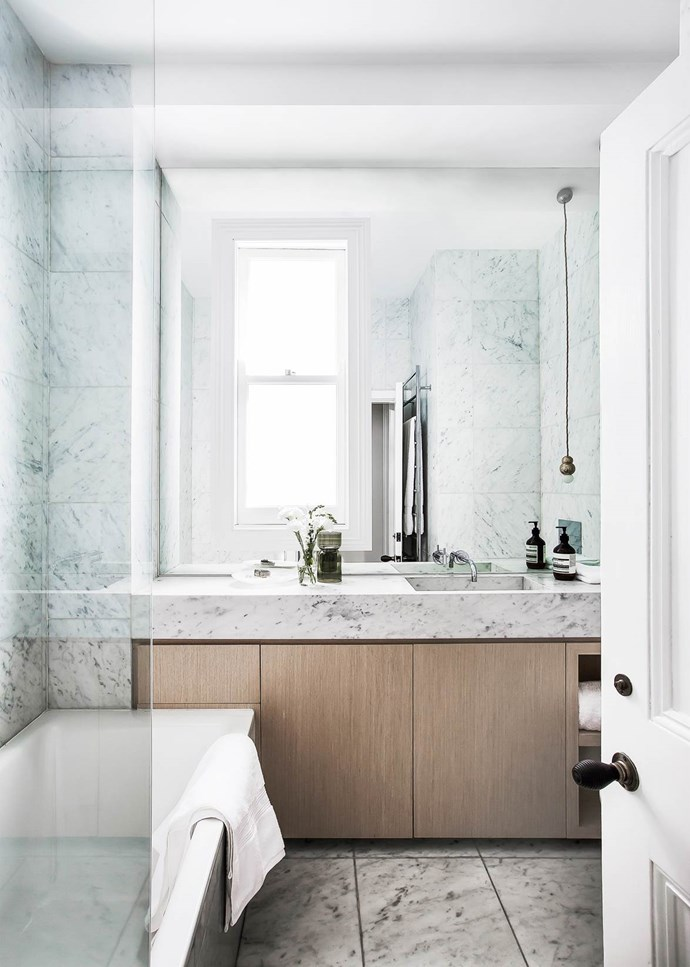 "Floor-to-ceiling Carrara marble, including a custom-made basin, feels wonderfully luxurious in this [elegant bathroom](https://www.homestolove.com.au/classic-parisian-style-unifies-a-victorian-terrace-4730|target=""_blank""). *Photograph*: Maree Homer 