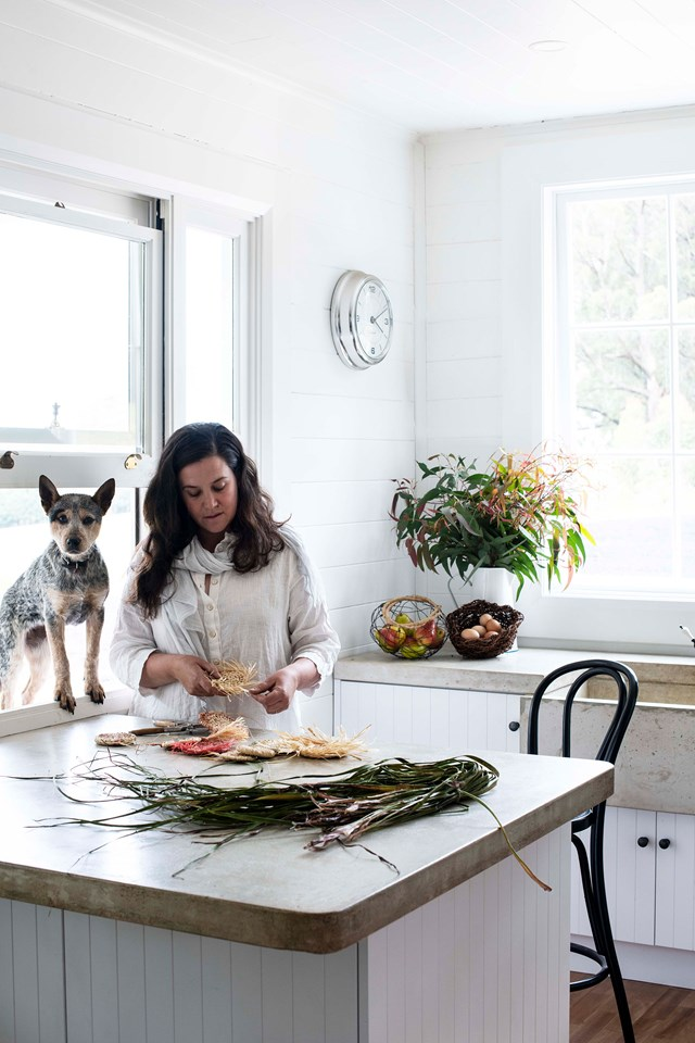 "Artist Brooke Munro grew up visiting her grandparents' farm where she would forage for bits of nature to make and play with. Her passion for creating beautiful pieces from foraged finds continues today, and here she is pictured in the kitchen of her [shaker style home](https://www.homestolove.com.au/contemporary-shaker-style-house-20212|target=""_blank""), alongside Peggy the cattle dog, weaving coasters from raffia."