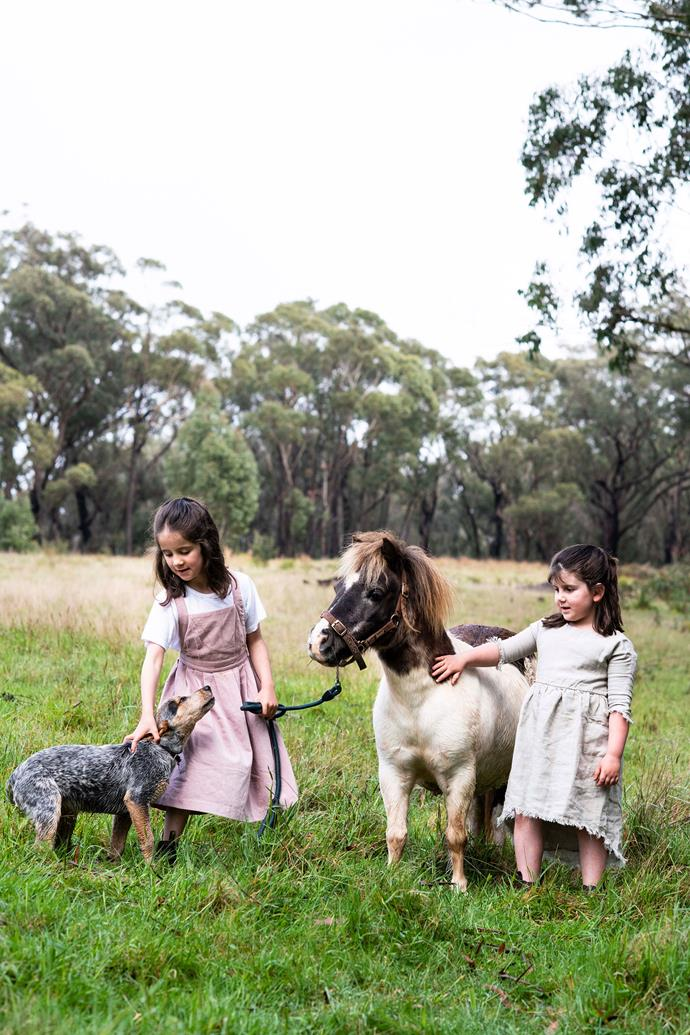 The couple's daughters Ruby and Arkie with Peggy the cattle dog and one of their beloved ponies, Flower.