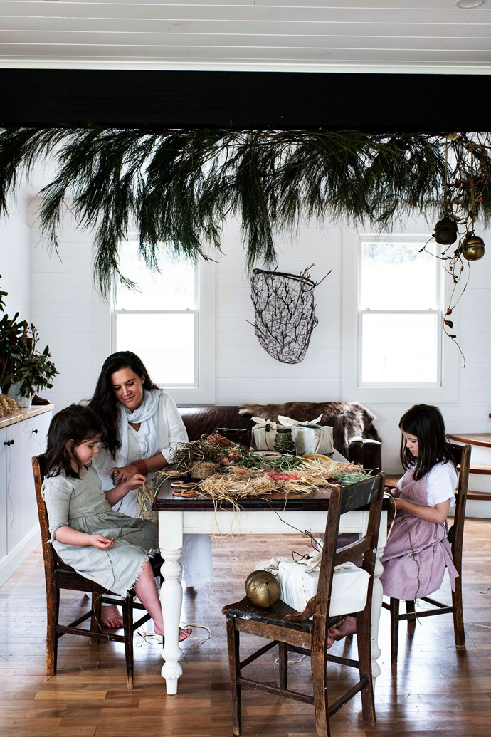 She-oak acts as a canopy above Arkie, Brooke and Ruby as they weave coasters using raffia and plant fibres. The table was a gift from Colin's godfather.