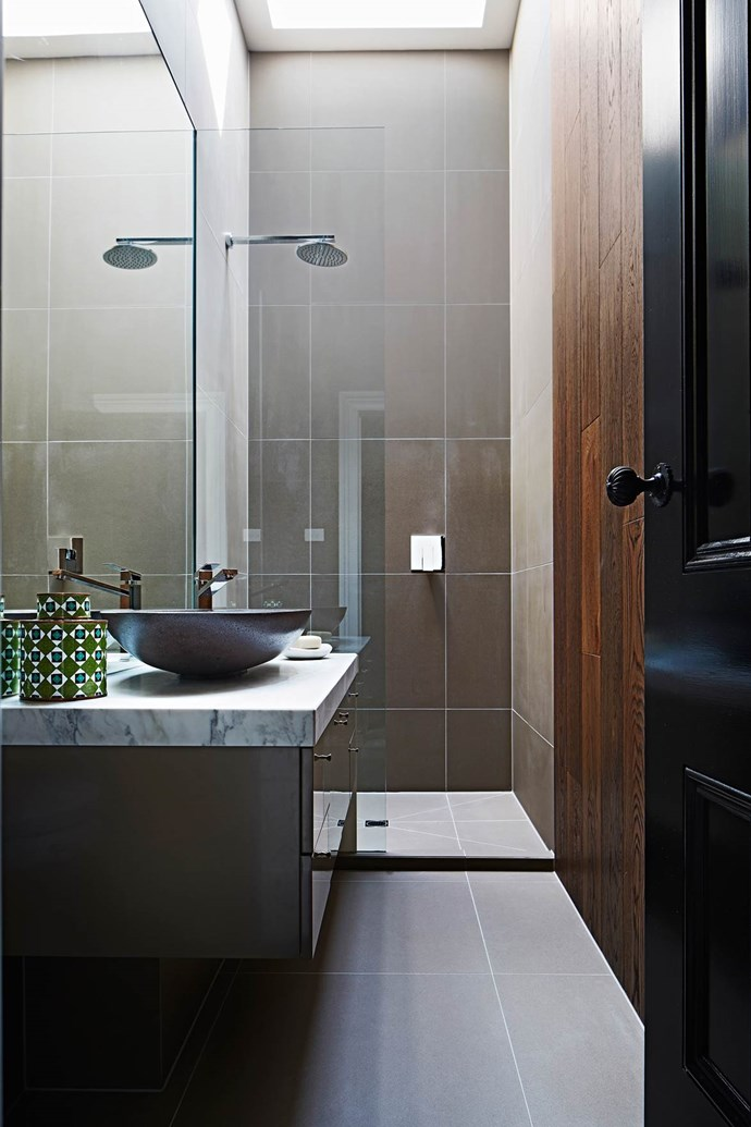 "A moisture-resistant engineered-timber wall is a lovely touch in this [moody bathroom](https://www.homestolove.com.au/melbourne-apartments-converted-into-family-home-3616|target=""_blank"") designed by owners Rupert and Kate Dowd. *Photograph*: Armelle Habib 