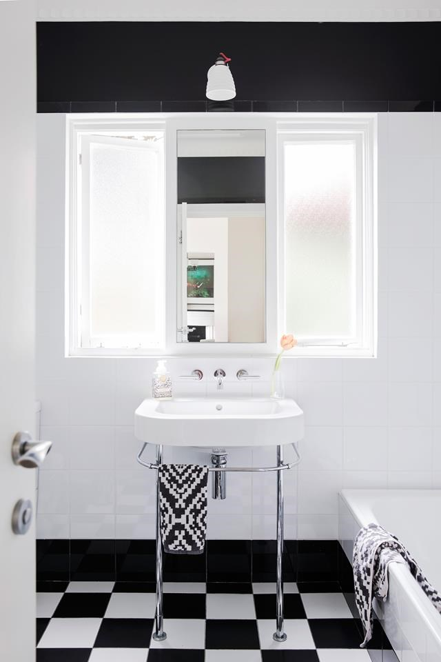 "In this [monochrome bathroom](https://www.homestolove.com.au/restoration-of-an-old-art-deco-home-6554|target=""_blank""), Fornasetti 'Fornasettiana' feature tiles over the bath add a dash of fun in the otherwise traditional black-and-white scheme. *Photograph*: Chris Warnes *Styling*: Kayla Gex"