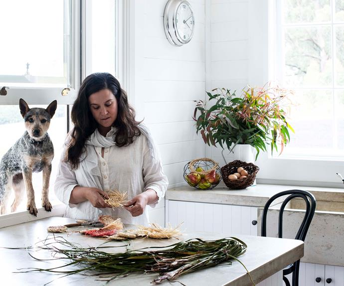 Woman in kitchen with kelpie in the window