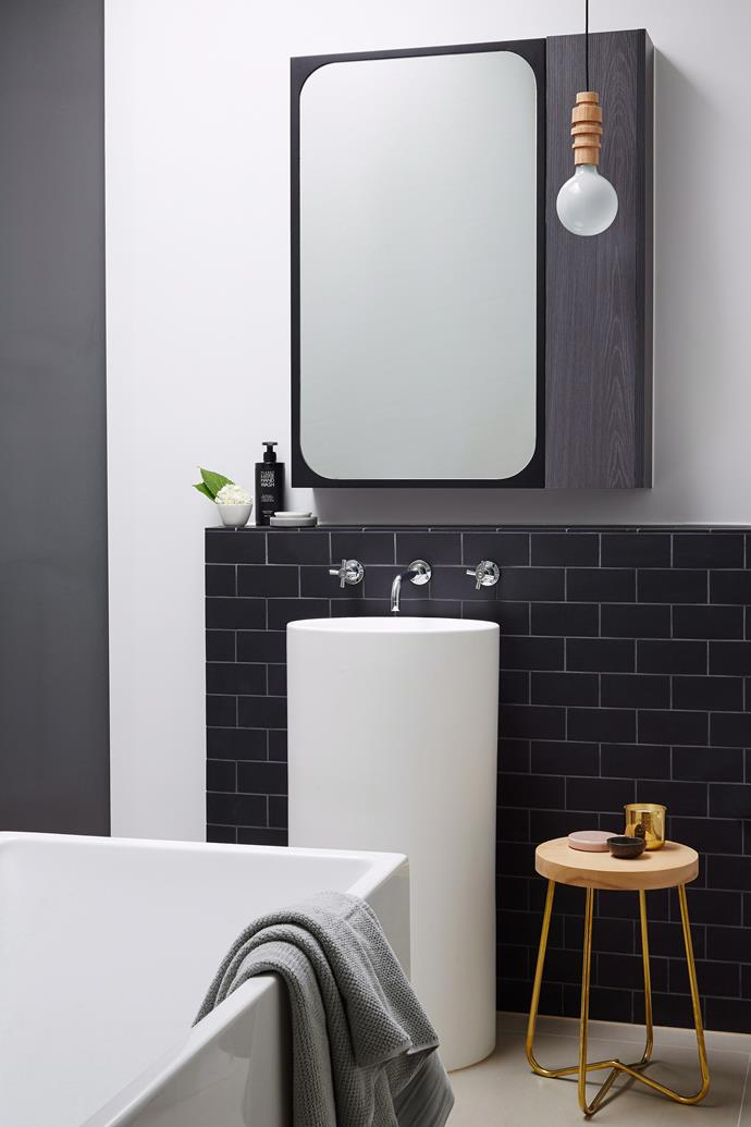 "Strong lines meet soft curves in this modern and edgy [monochrome bathroom design](https://www.homestolove.com.au/monochrome-bathrooms-6390|target=""_blank""), where bold tiles and touches of timber add graphic interest."