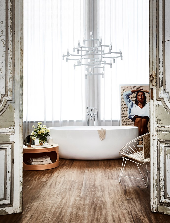 Create a day spa feeling in your bathroom with decorative finishings. Think timber-look tiles on the floor, sheer curtains at the windows, a coffee table to store all your tub-time essentials and a striking chandelier overhead. But not all lighting can be hung over a bath – check with your electrician first. *Photo:* Kristina Soljo