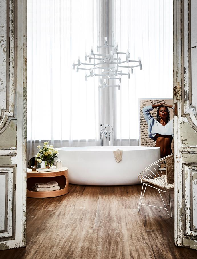 Create a day spa feeling in your bathroom with decorative finishings. Think timber-look tiles on the floor, sheer curtains at the windows, a coffee table to store all your tub-time essentials and a striking chandelier overhead. But not all lighting can be hung over a bath – check with your electrician first.