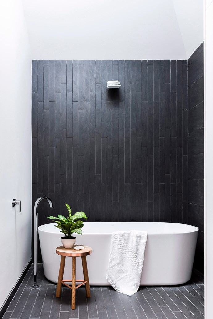 For walls that go for days, long, vertical tiles are your friend. This reno has also incorporated a lightwell to illuminate the charcoal ceramics, while at night-time, in-built LED lighting makes the rain shower glisten. *Photo:* Maree Homer