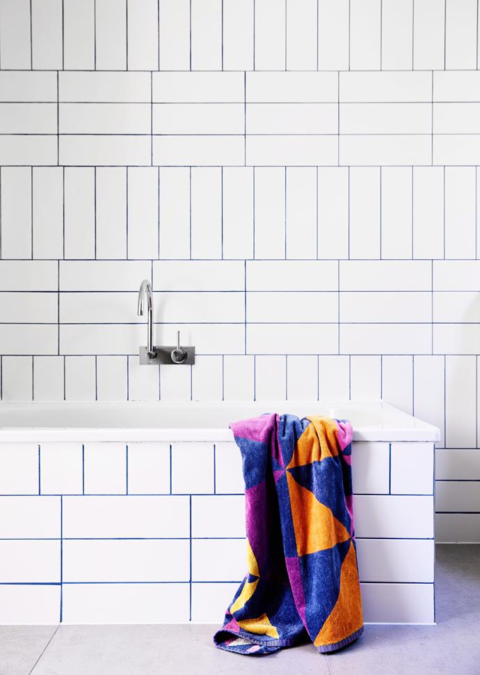 "Jazz up some otherwise plain white [subway tiles by laying them in varying patterns](https://www.homestolove.com.au/subway-tile-pattern-ideas-20203|target=""_blank""), and finishing with a coloured grout. Do the same around your tub for a cohesive and impactful look."