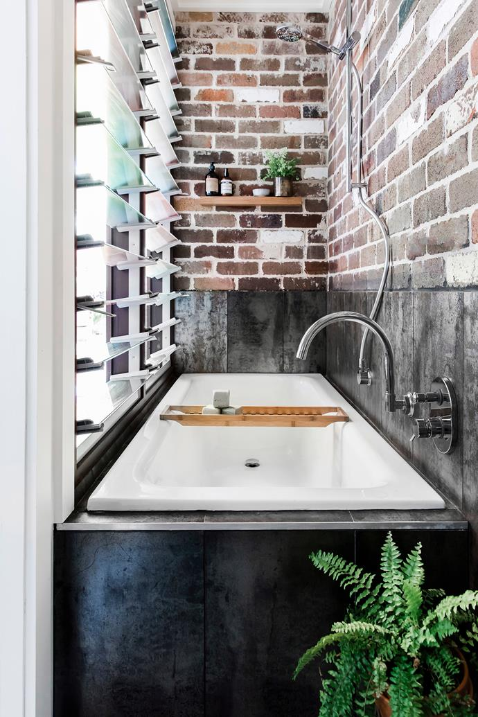 "Don't let a tricky space get the better of you! This clever [bath and shower design](https://www.homestolove.com.au/inset-bathtubs-19355|target=""_blank"") makes great use of its windowside position, with the exposed brick wall adding a nice industrial touch."