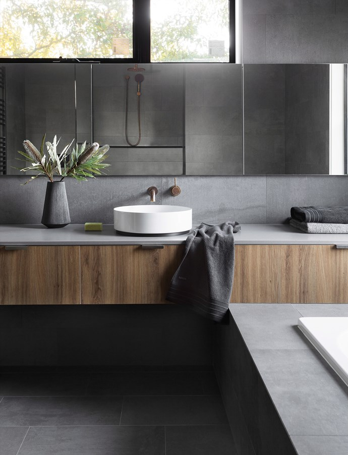 Bathrooms don't have to be sleek and shiny. Take this stunning room with its glorious mixture of textures – the concrete-look tiles and benchtop provide a lovely contrast against the walnut veneer cabinetry. It's also a combo that works well in a kitchen or laundry, so you can continue the look throughout your home. *Photo:* Martina Gemmola