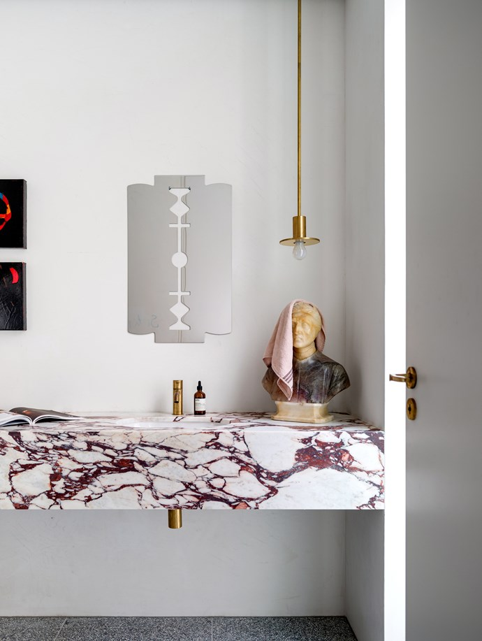 Simple white walls in this decadent chamber allow the pink-marbled vanity to shine. Meanwhile, artworks and design objects are used in surprising ways – the razor mirror doubles as an artwork for the wall, while the Dante sculpture becomes a convenient hand-towel holder. *Photo:* Justin Alexander / *bauersyndication.com.au*