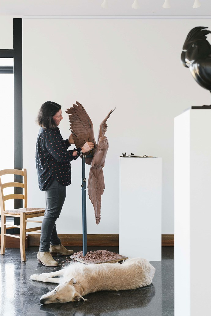 Lucy at work on the clay mould of a macaw parrot in her studio with Sylvia the staghound at her feet.