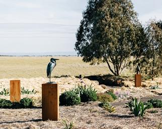 Bronze bird sculpture on plinth in rural garden
