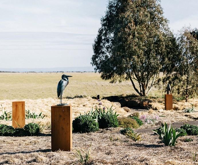 Bronze bird sculpture on plinth in rural garden