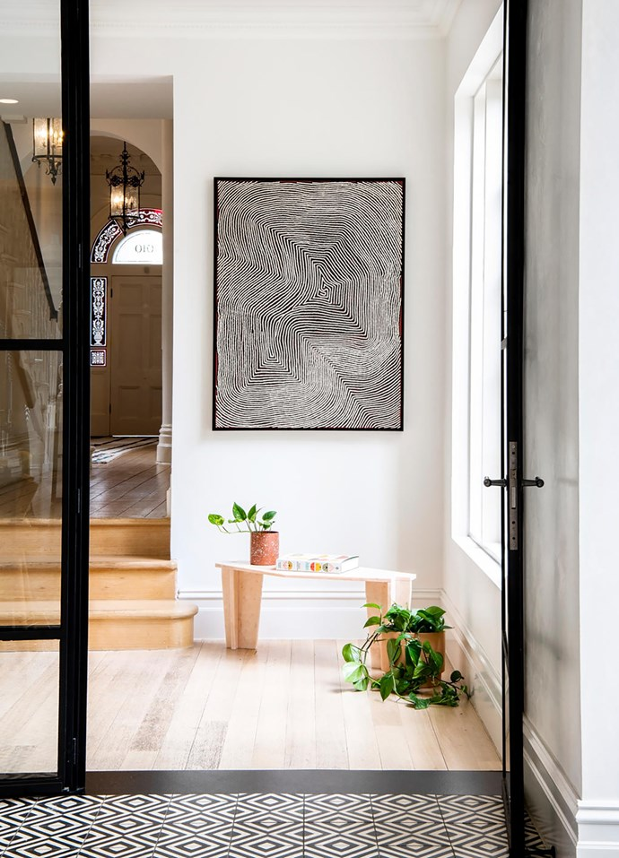In the hallway under a work by Warlimpirrnga Tjapaltjarri is an Italian marble table sourced by Simone. Ceramics from Modern Times and Pépite sit on the table by Studio Thomas Lentini.