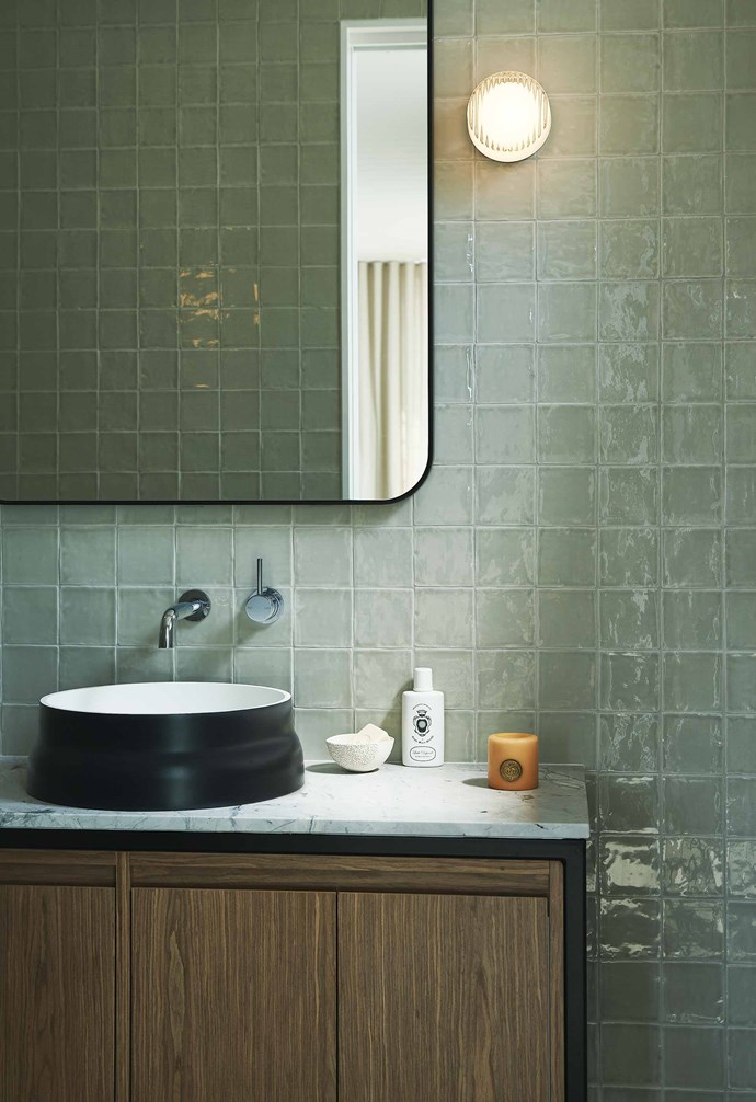 **Cool change** Textural wall tiles create a sense of serenity to the bathroom, designed by Tom Mark Henry Studio. Encased in timber and marble, the vanity unit plays with different natural materials. *Photography: Damian Bennett*.