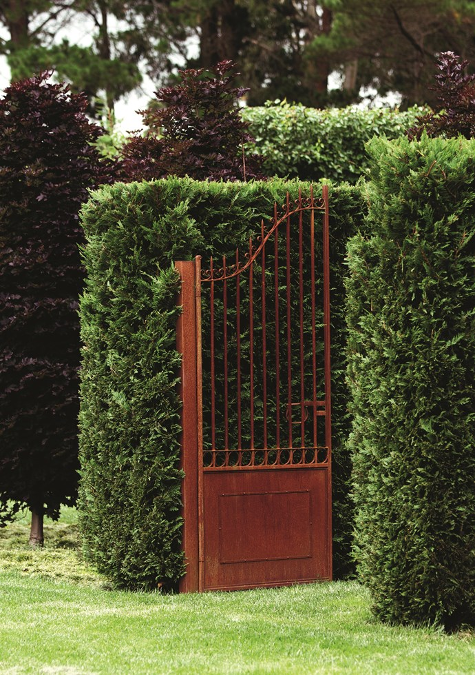 Tall iron gates with a rust finish were custom made for the garden.