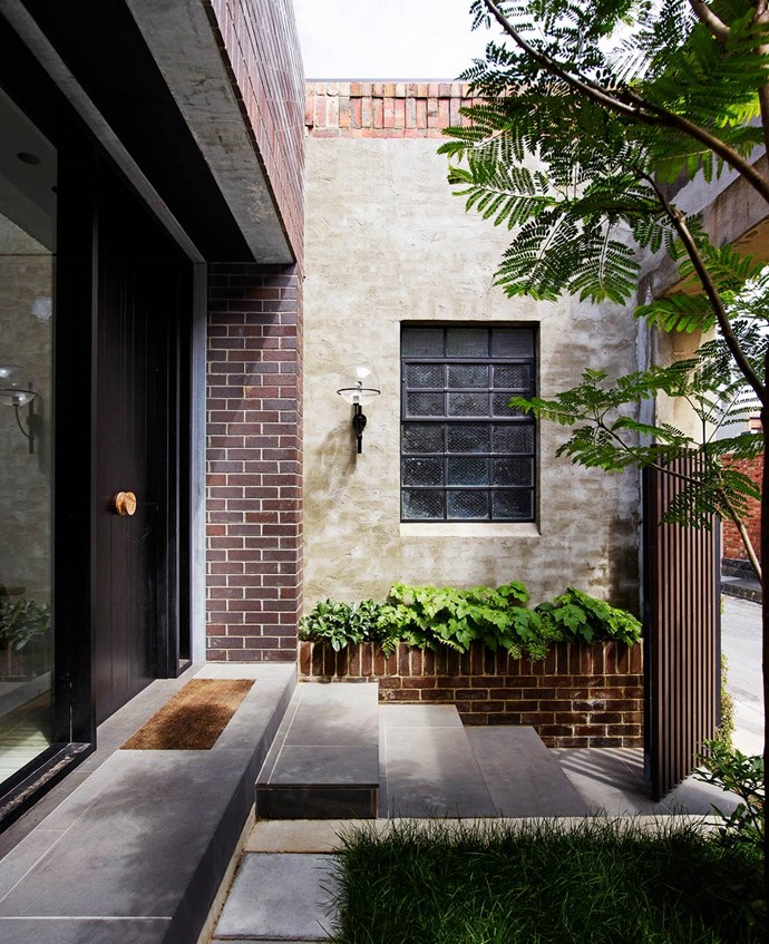Architects Kerry Phelan and Stephen Javens, directors of K.P.D.O., created a home out of the ramshackle garage of an old military building in Melbourne. The entrance to the property features a small courtyard hidden behind a dark timber gate. *Photograph*: Richard Powers. From *Belle* June/July 2016.