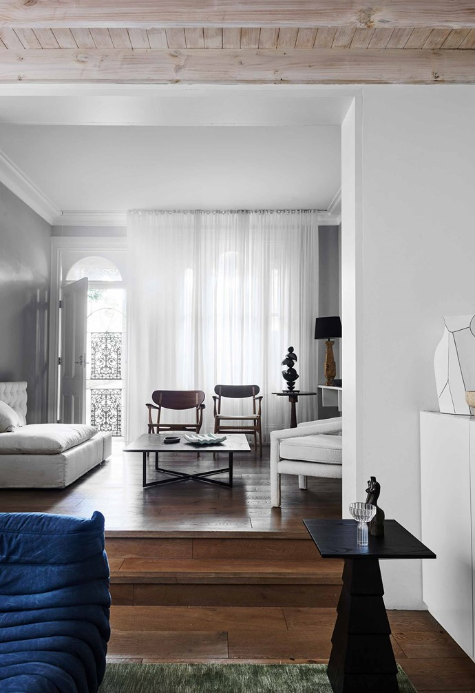 """**Formal living** Now that the home's entrance is on the side, the outdoor area at the front is closed off from the street. Floor-to-ceiling curtains and a Frigerio sofa from [Pure Interiors](https://pureinteriors.com.au/