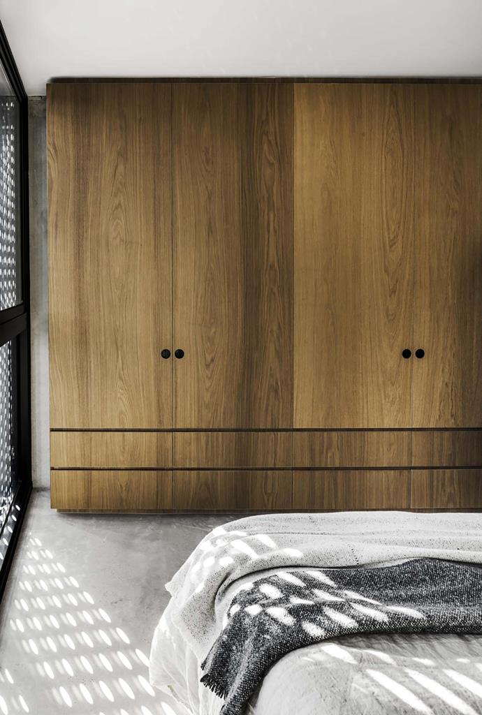 Timber joinery lends a note of warmth to the bedroom's sleek, utilitarian shades of grey.