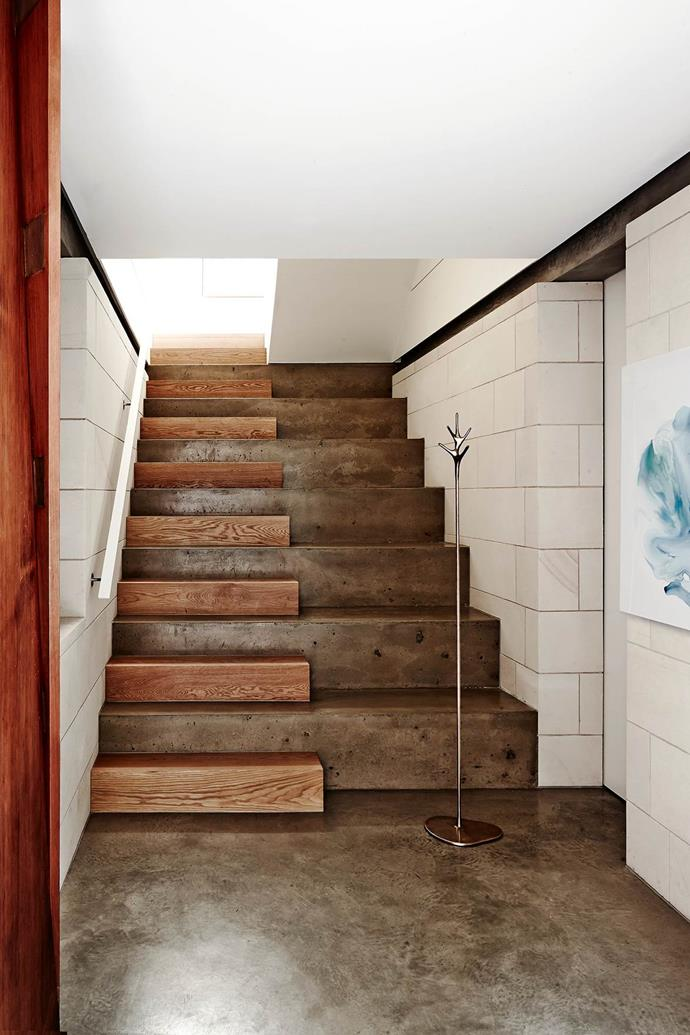 "Oak and polished concrete stairs make a statement in the entry to this [beach house](https://www.homestolove.com.au/contemporary-beach-house-with-a-luxury-twist-3612|target=""_blank"") conceived by Brett Mickan. The concrete was tinted a taupe shade to mimic the nearby sandstone cliffs. *Photograph*: Will Horner. From *Belle* May 2016."