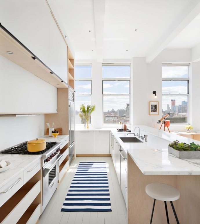"""In the open-plan kitchen, light oak cabinetry and white timber floors create Scandinavian style vibe while the Carrara marble benchtops add a luxe touch. *Photo:* [DDreps](http://ddreps.com/ target=""""_blank"""" rel=""""nofollow"""")"""