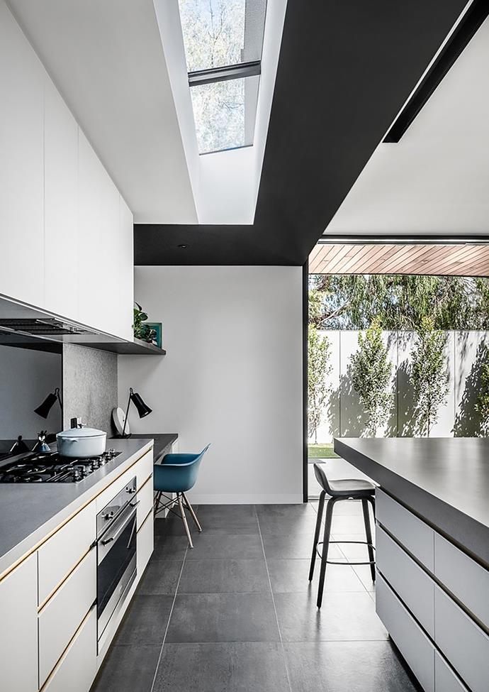 Appliances and storage are concealed, with the main preparation space located directly under the feature skylight, flooding natural light into the heart of the home.
